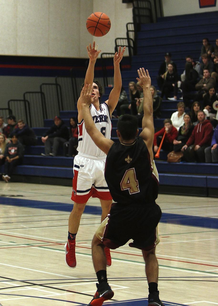 Basketball player performing jump-shot over defender (Source: Pixabay, Keith JJ)
